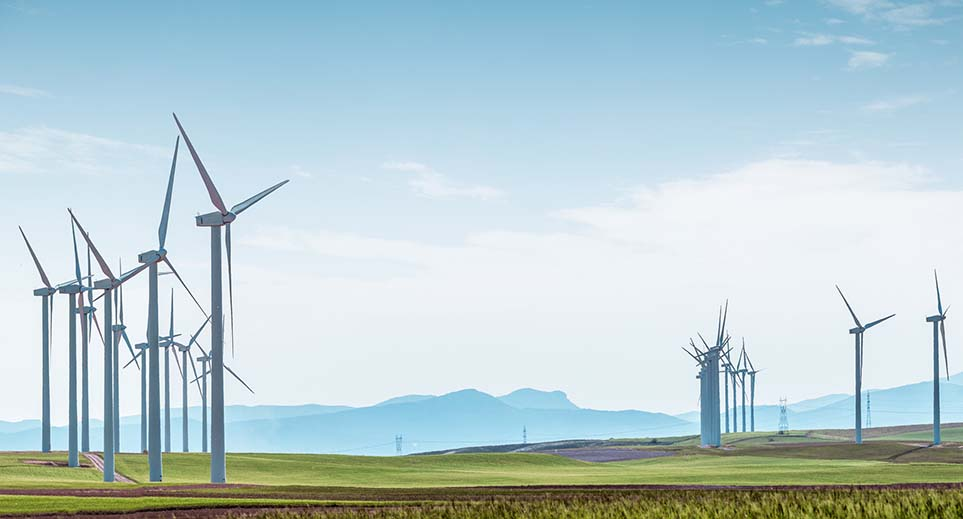 Rows of wind turbines on green boundless fields on background of blue cloudy sky and distant hills. Alternative energy source, production and power generation. Ecology and environment.